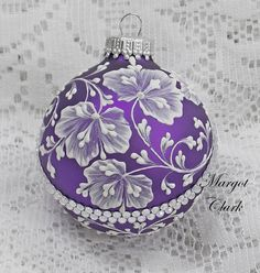 Margot Clark created this rich, purple colored glass ornament with White 3D texture painted MUD floral design with added bling. Each ornament created is a one-of-a-kind. The texture medium and paint brush I use to paint the ornaments were both created to my specifications. My signature M is located on the bottom of the ornament. Gift boxed. Measures 2 1/2 x 2 1/2 Ornament weight is 2 ounces.