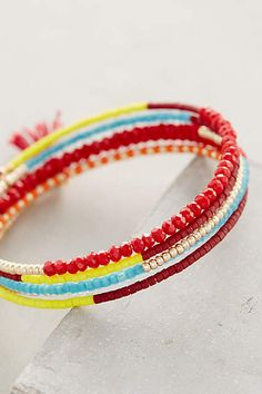 "DIY Inspiration: Anthro Jane Wire Wrap Bracelet, handmade in U.S. by Sashi. Glass & plastic seed beads w/ cotton tassel threaded on memory wire. 0.5""W x 2""D"