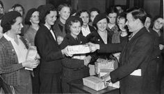 Walter Reuther distributes packets of leaflets to members of the UAW Women's Auxiliary Brigade for distribution at the Ford Rouge Plant, two hours prior to the Battle of the Overpass. 1937-05-26. Walter P. Reuther Library, Wayne State University.