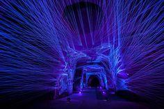 Fleuve Céleste, Julien salaud, 2015, 45km de fils de cotons traités pour briller quand il sont éclairés par de la lumière ultraviolette et 65 000 clous pour les tenir en place et leur donner la forme de personnages et d'animaux dans une cave de 60m de long. installation de fils ultraviolets