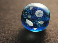とんぼ玉アーティスト・増永元(ますなが げん)さんの作品。深い蒼色の海に浮かぶミズクラゲのとんぼ玉は、はっと息をのむほど美しく、その世界観にひきこまれます。