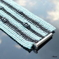 Ikarus Náramek šitý z tisíců luxusních droboučkých japonských rokajlových korálků TOHO Treasure v barvách tyrkysová, černá a antracit. Ve vzorku použity maškané kuličky antracitové barvy. Šířka náramku je 4,6 cm a délka 19,5 cm vč. zapínání. Náramek má zasouvací magnetické zapínání.
