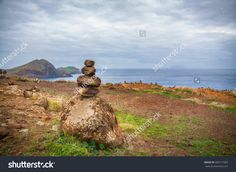 Rough stones in balance on the ocean shore. Stone tower on the shore of the Atlantic Ocean. Portugal, Madeira Island