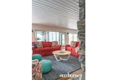 Durable and easy-to-clean slipcovers in bright coral with printed pillows enliven the living room of this renovated lakeside home.    http://www.ourhomes.ca/articles/build/article/whitewashed-weekender-ripe-with-rustic-chandeliers