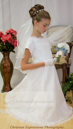satin short sleeves first holy communion dress with beautiful lace overlay accented with beading. Scalloped organza trim. Organza bow in back.  Fully lined. Tea length. Available exclusively at Christian Expressions http://www.firstcommunions.com/FirstCommunionDresses-6810.aspx