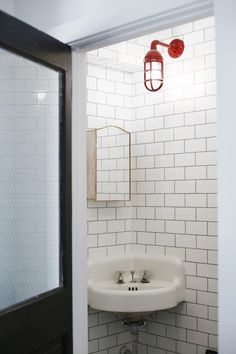 With its bold red finish, a wall sconce captures attention by contrasting with the white tile, cast iron corner sink, and antique medicine cabinet. Black Wall Sconce, Vintage Wall Sconces, Indoor Wall Sconces, Rustic Wall Sconces, Candle Wall Sconces, Outdoor Wall Sconce, Wall Sconce Lighting, Bathroom Wall Cabinets, Bathroom Wall Sconces