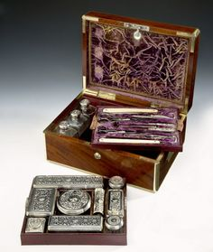 Mahogany Gentleman's Dressing Box with brass carrying handles. The lid opening reveals a velvet and leather interior with twelve engraved silver topped bottles, all with an engraving of an oak tree. The top tray lifts out to another tray of tools, including ivory handled cut throat razors, scissors, boot pulls, tongue scrapper and others. Inside the lid is a fold down panel with a section on the reverse for letters etc. London ca. 1827