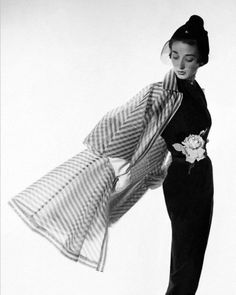 Circa April 1950, New York, New York, USA --- Model Dorian Leigh wearing a black rayon crepe sheath dress and black and white striped organdy coat by Bonnie Cashin with a small veiled hat by John Frederics; a large rose is attached at the waist of the dress. --- Image by © Condé Nast Archive/Corbis