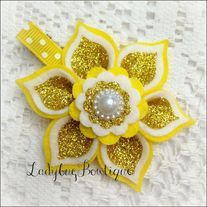 3-inch flower is made with soft wool-blend felt and super-sparkling glitter fabric that does not shed. It is attached to large alligator clip that has been partially-lined with grosgrain ribbon, leaving the bottom prong exposed.