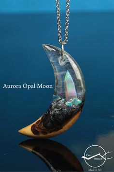 A world of shifting colors hidden in a shard of aurora opal. There is a small world hidden within every pendant we make. Handmade using reclaimed wood and locally sourced resin. Each necklace is painstakingly assembled before being cast in iridescent resins, then carved and polished to a glass-like finish. #resinart #auroraopal #moon #opalmoon