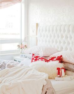 cozy white bed and stenciled wall behind.
