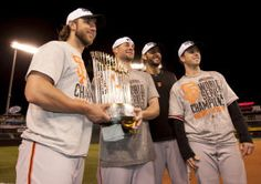 San Francisco Giants' Madison Bumgarner, from left, Ryan Vogelsong, Michael Morse and Buster Posey hold the Comissioner's Trophy following