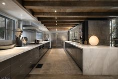 Stylish and sleek: The kitchen is where the newer elements of the home's design can be seen most as it features an impossible long marble island and a matching counter with sleek cabinetry