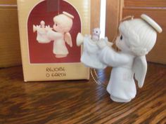 Precious Moments Rejoice O Earth Ornament by Enesco. Made in 1988 and retired several years later. This adorable Precious Moments Angel is holding
