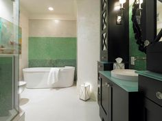 Bathroom: Gradients Of Green. bathroom color. green mosaic tile. freestanding tub. white floor. black bathroom cabinet. glass vanity top.