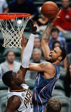 Charlotte Bobcats center Tyson Chandler, right, puts up a shot over Indiana Pacers center Roy Hibbert