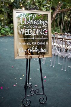 Al Fresco Black-Tie Glamour | Miami + Fort Lauderdale, FL | Welcome to our wedding | Thank  you for joinging our celebration wedding sign on a mirror and easel with ghost chairs and cross back vineyard chairs