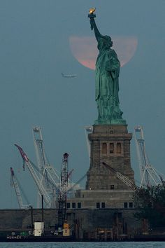 "With a plane approaching Newark Airport, a ""super moon"" sets behind a cloud and the Statue of Liberty on Sunday, June 23, 2013, in New York. The larger than normal moon called a ""super moon"" happens only once this year as the moon on its elliptical orbit is at its closest point to earth and is 13.5 percent larger than usual. (AP Photo/Julio Cortez)"