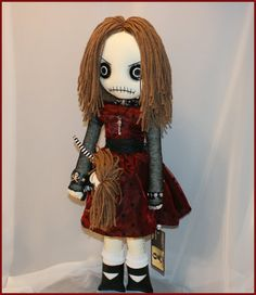 This tattered rag doll is completely hand stitched, stands 22 inches tall, has vintage button eyes, and yarn hair.  Shes wearing a red & black polka-dot dress, black panties, white bobby socks, and black leather shoes.  Her accessories consist of a leather studded choker with a pewter skull, a pewter skeleton key necklace, and two leather studded wrist cuffs one with a skull & crossbones. She carries a hand stitched dolly who also has vintage button eyes and yarn hair, shes dressed in a…