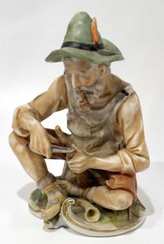 Continental porcelain figure of a Shepherd carving a piece of wood.