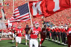 Ethan Armstrong carries the American flag into the Homecoming Game