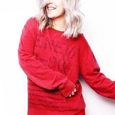 Loira de cabelo platinado em um fundo branco iluminado com moletom vermelho