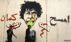 """Riot police walk past new graffiti on Cairo's Mohammed Mahmoud street saying: """"Erase more, you cowardly regime"""""""