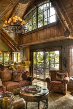 great natural light - love windows over kitchen counters, wood trim around sliding door, fish net on wall, open to kitchen, moose pillow, round coffee table.... very cozy