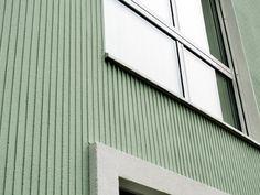 Herkömmliche Baustoffe in edelster Form: Eine grüngraue, mit einer vertikal gerillten Kammstruktur versehene Putzschicht bedeckt die konventionelle Aussendämmung. Der Putz wurde unterbruchsfrei über die 15m hohe Fassade gezogen und von Hand nachgeschliffe