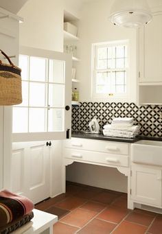 This dog nook is tucked away in the world's cutest laundry room and is framed with decorative braces. It blends beautifully with a Dutch door, a farmhouse sink and a geometric backsplash.