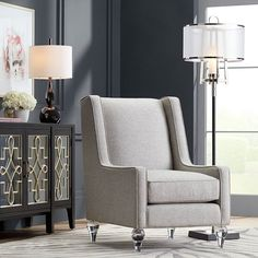 Take a seat, the ultimate in elegance is here.  . Graham Gunmetal Table Lamp - 74N87 Monterey Floor Lamp - 72W32 Kallie Grey Accent Chair - 47R79