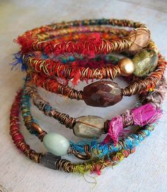 Bracelets with semi-precious stones or beads. Wrapped in silk and metallic thread.