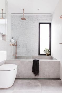 #2: This small but deep bath was built using large format grey tiles from TeraNova Tiles. Brodware 'City Stik' tapware in rose gold warms up the soft grey palette. See the rest of this home here.