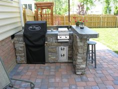 how to build a outdoor bar and grill | This L-shaped outdoor kitchen includes a built-in grill, burner and ...