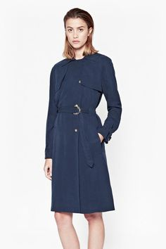 Soft, lightweight trench coat. Double-breasted metallic popper fastenings with exposed off-centre placket of metallic rivets. Collar and cuffs with adjustable straps and semicircular metallic fastenings. Front inseam pockets. Waist belt with semicircular metallic fastenings. Storm flaps at chest and side splits at hemline.