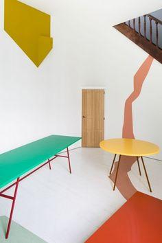 Fien Muller und Hannes van Severen leben in einer alten Scheune mit rotweiß gestreiftem Tor. Sie haben zwei Kinder und wenn sie an ihrem runden Holztisch mit gedrechselten Beinen sitzen, dann essen sie zu gerne Pflaumencrumble. Das allein sind aber nicht ihre einzigen Herzdinge. Das andere Projekt liegt in der Werkstatt. Dort entwerfen sie ihre Möbel. [...]