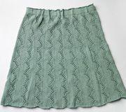 """Når først man er kommet i gang, er det nemt at strikke nederdelens smukke hulmønster. Garnet er en blanding af viskose, bomuld og hør, som """"falder"""" flot"""
