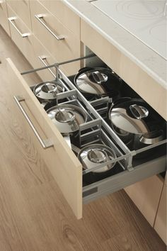 A close-up of three well-lit kitchen drawers are pulled out. Install ...
