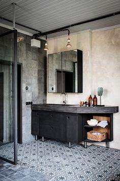 Baño con suelo de azulejos hidráulicos, paredes de cerámica efecto cemento y mobiliario negro.