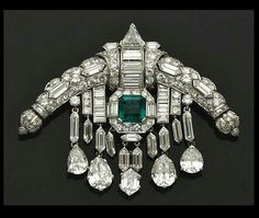 """The Queen`s Diamond & Emerald """"Sarpech"""" brooch. A sarpech is really a turban ornament, worn by Hindu or Muslim Princes. this one was made in 1920 to an Art-Deco design, it features multiple cuts of diamonds in platinum & white gold. In the centre is a square emerald framed in diamonds & sitting between diamond tassels with pear-shaped diamond pendants."""