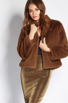 A faux fur coat featuring a mock neck, on-seam pockets, satin lining, long sleeves, a single hook front, and a boxy silhouette.