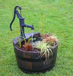 A Wooden Barrel Plant Filled Garden Water Feature