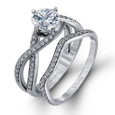 This sparkling modern white gold engagement ring and wedding band set features an eye-catching twisted design accented by .22 ctw of shimmering round cut white diamonds. Simon G Style # MR1394