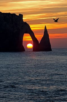 Coucher du soleil dans l'arche de la falaise d'amont à Etretat.