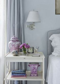 Interior Design by Susan Reddick Design uses bright pops of orchid colors as accessories to liven up a bedroom with grey walls and curtains