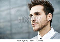 Joven guapo cerrar retrato (piercing en la oreja y labios)