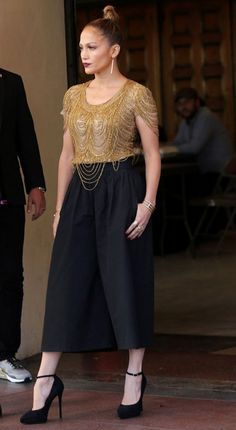 Trending Fashion Style: High-waisted Pants.  - Jennifer Lopez in Naeem Khan Pre Fall 2014 golden glitzy fringed beaded sequin threads top with Alice + Olivia high-waist cropped wide-leg black trousers.