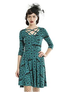 <div>This fun and flirty dress from <i>Fantastic Beasts And Where To Find Them</i> symbolizes the movie perfectly. The stretchy fit and flare skater dress has half-sleeves and a strappy neck detail that fits right into the 1920s era film. The elegant emerald dress has an allover black print featuring the New York City skyline, the No-Maj symbol, Newt Scamander's briefcase, the MACUSA logo and the Owl Post Office logo .While the pockets may not be big enough to hold a wand, they'll still...