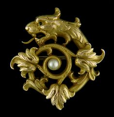 A fierce lion-headed serpent with a tail of flame-like acanthus leaves warily guards this brooch with a jealous green eye. A glowing pearl is set in the center. Created by Carter, Howe in 14kt gold, circa 1890.