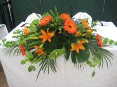 Long Low Table Arrangement Gerberas, Asiatic Lilies, Anthuriums, Molucella(Bells of Ireland), Palm leaves, Monstera leaves.
